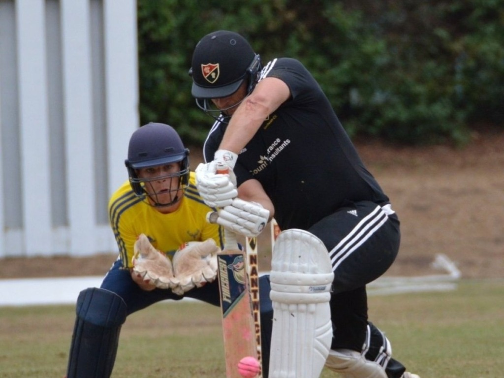 Two cricket players blocking the ball during game